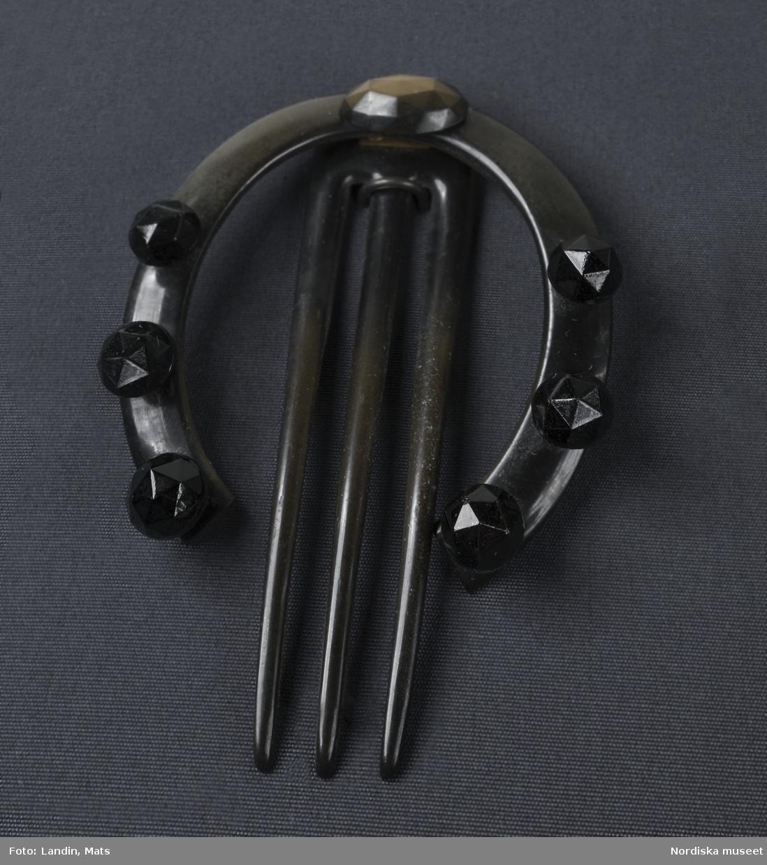 Smycke. Kam. Prydnadskam i horn i form av en hästsko. Föremål ur Nordiska museets samlingar invnr.NM.0087491 .