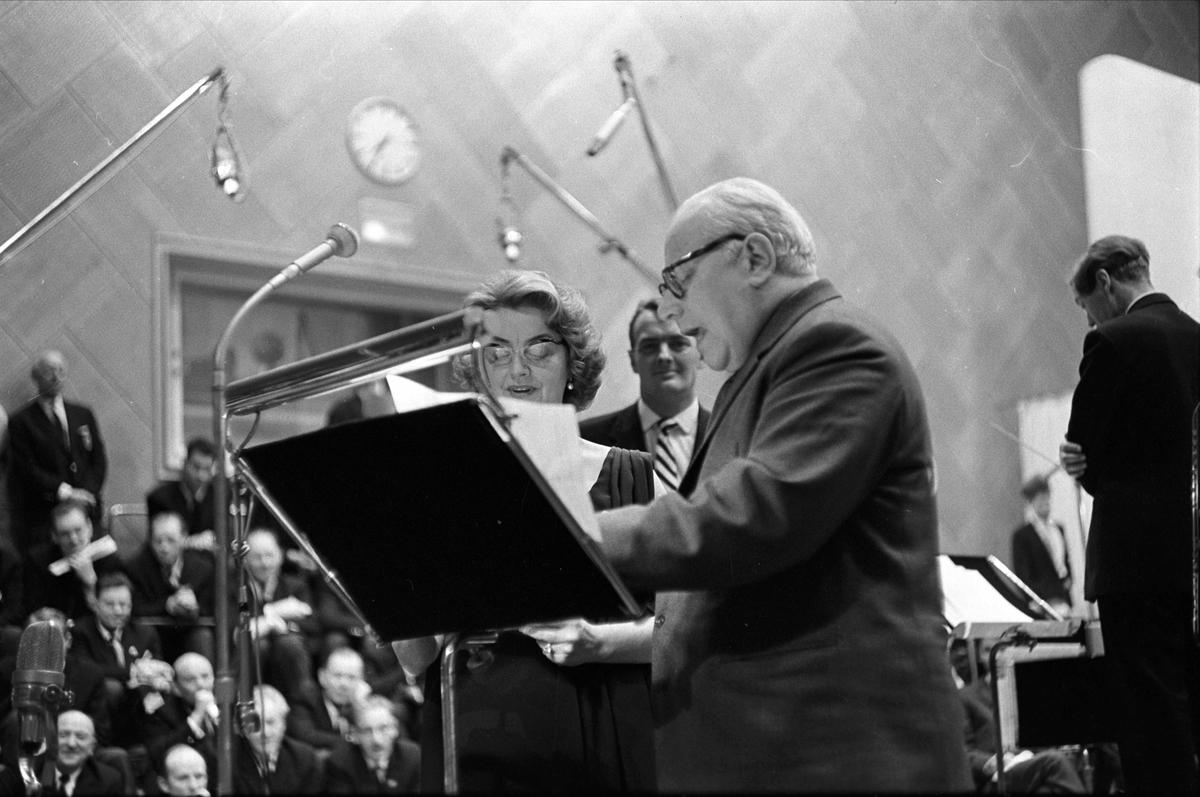 """Kringkastingens """"Vi går ombord"""", juleprogram, Oslo, 24.12.1962. Mann og kvinne ved mikrofonen, Erik Bye i bakgrunnen."""