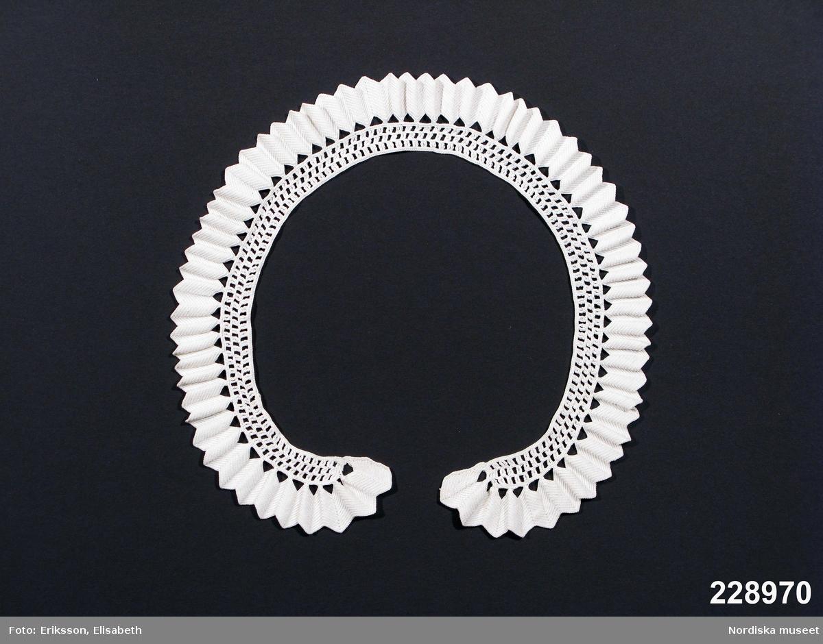 Av vitt tunt bomullsgarn, smal något svängd krage virkad innerst mot halsen med glesa stoplmaskor i tre varv och i ytterkant uddkant virkad av fasta maskor som ger ett tätt bandliknande utseende som också är något veckat genom att det innehåller fler maskor än inre delen. Var tydligen ett inte alltför ovanligt mönster, fler exemplar med tillhörande små manschetter finns. Troligen från 1860-70-talet, då smala kragar var modernt. /2009-02-03 Berit Eldvik