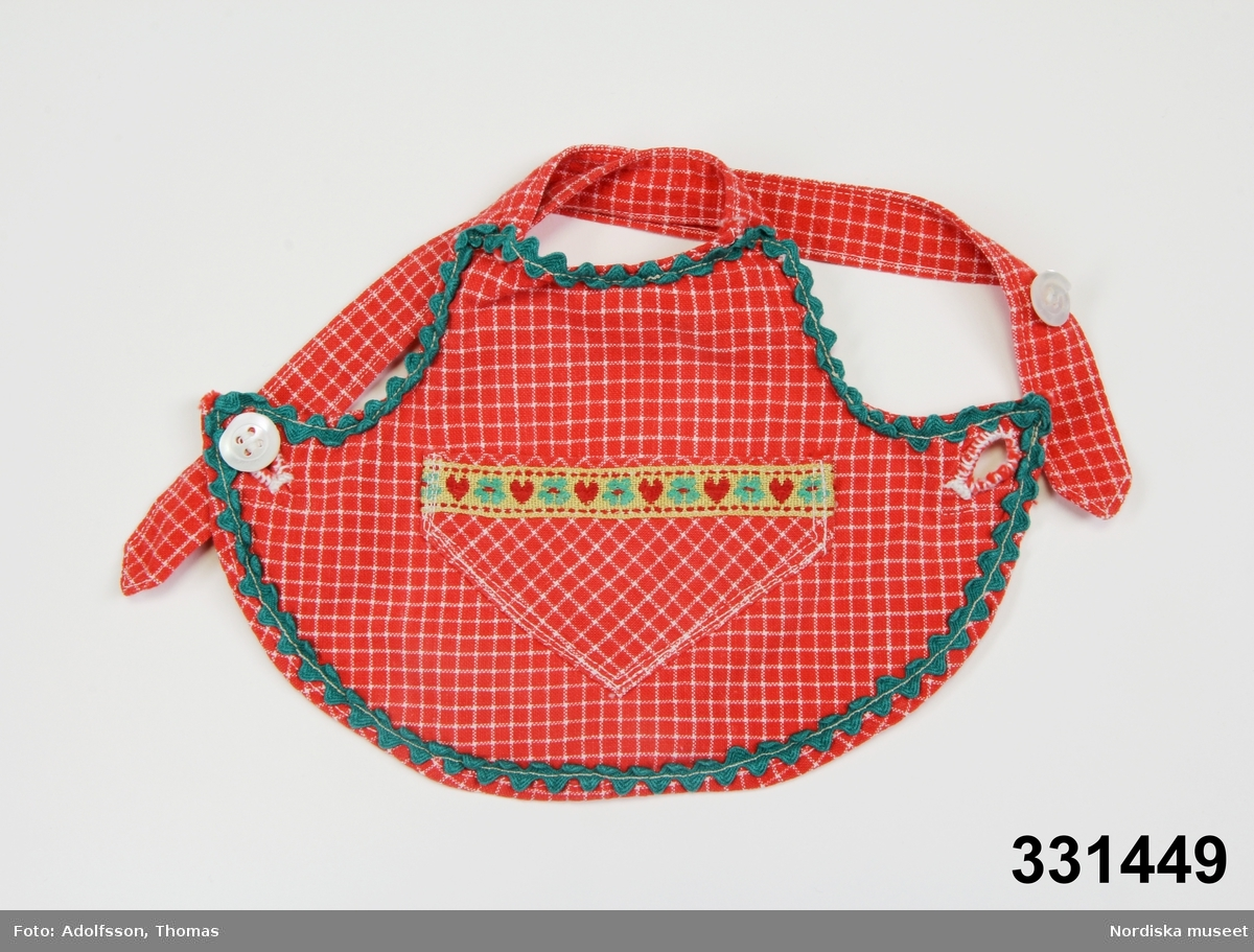 Rutigt dockförkläde kantat med gansband och med påsydd ficka och dekorband med blomsterbrodyr. Med knytband och knappar.  /Karin Dern 2011-09-13