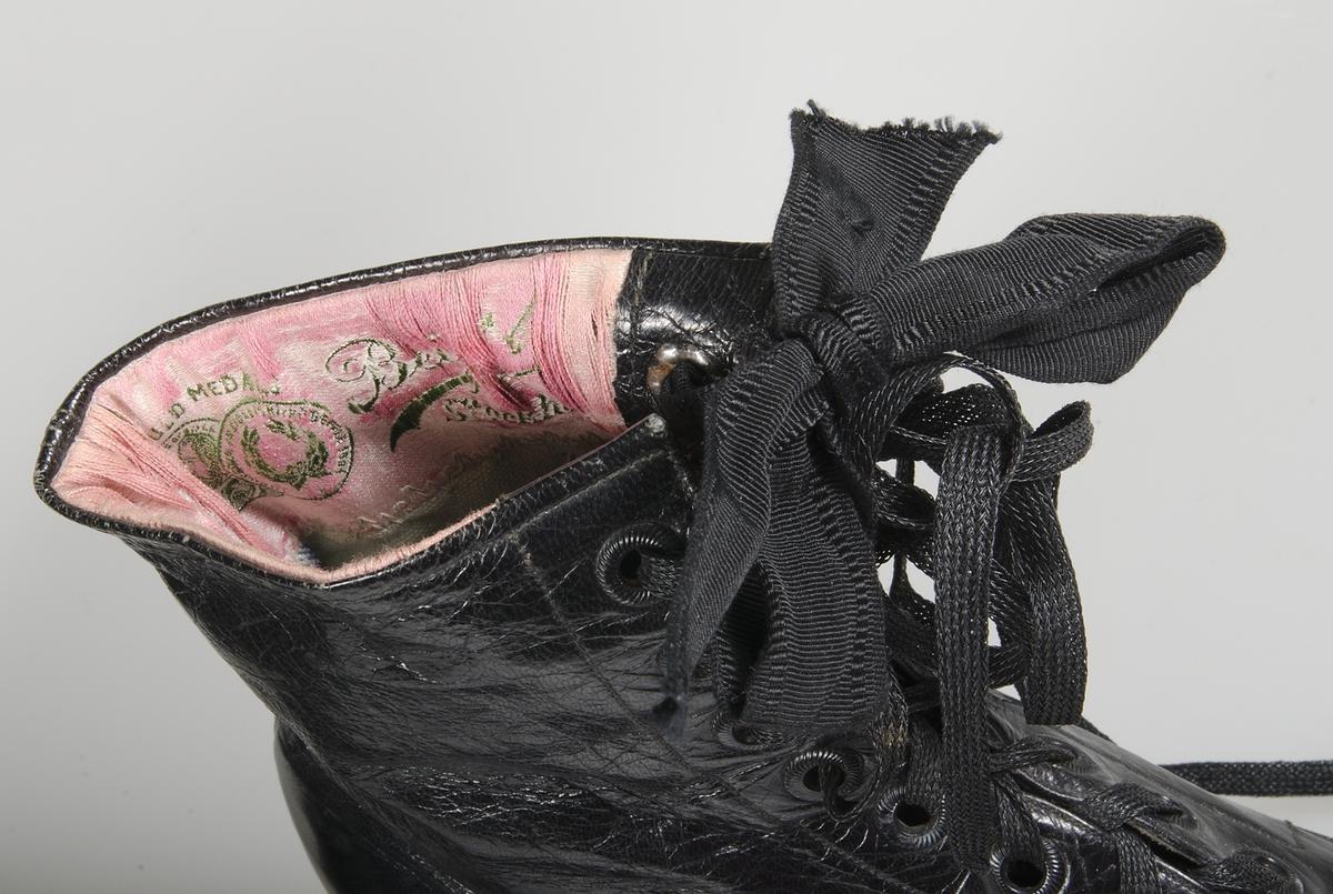 Av svart läder. Svart lädersula. Fodrade med vit lärft och rosa siden med grön invävd text: Beijer Stockholm.