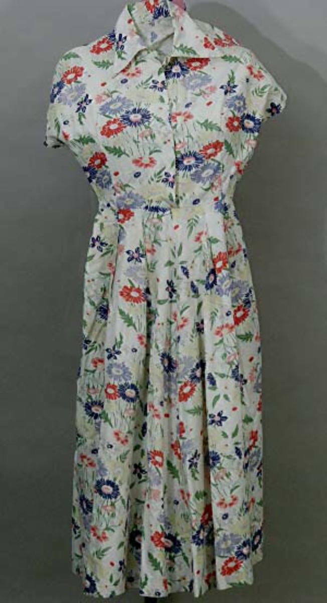 Klänning av bomullslärft med tryckt blommigt mönster i rött, blått, gult och grönt  på vit botten. Figursytt liv med kort kimonoärm, rund ringning med krage med snibb, knäppt fram med dold knäppning, 4 vita knappar , tryckknapp överst i halsen. Vid veckad utställd kjol i fyra våder. Vecken upptill nedsydda en bit. Maskinsydd.