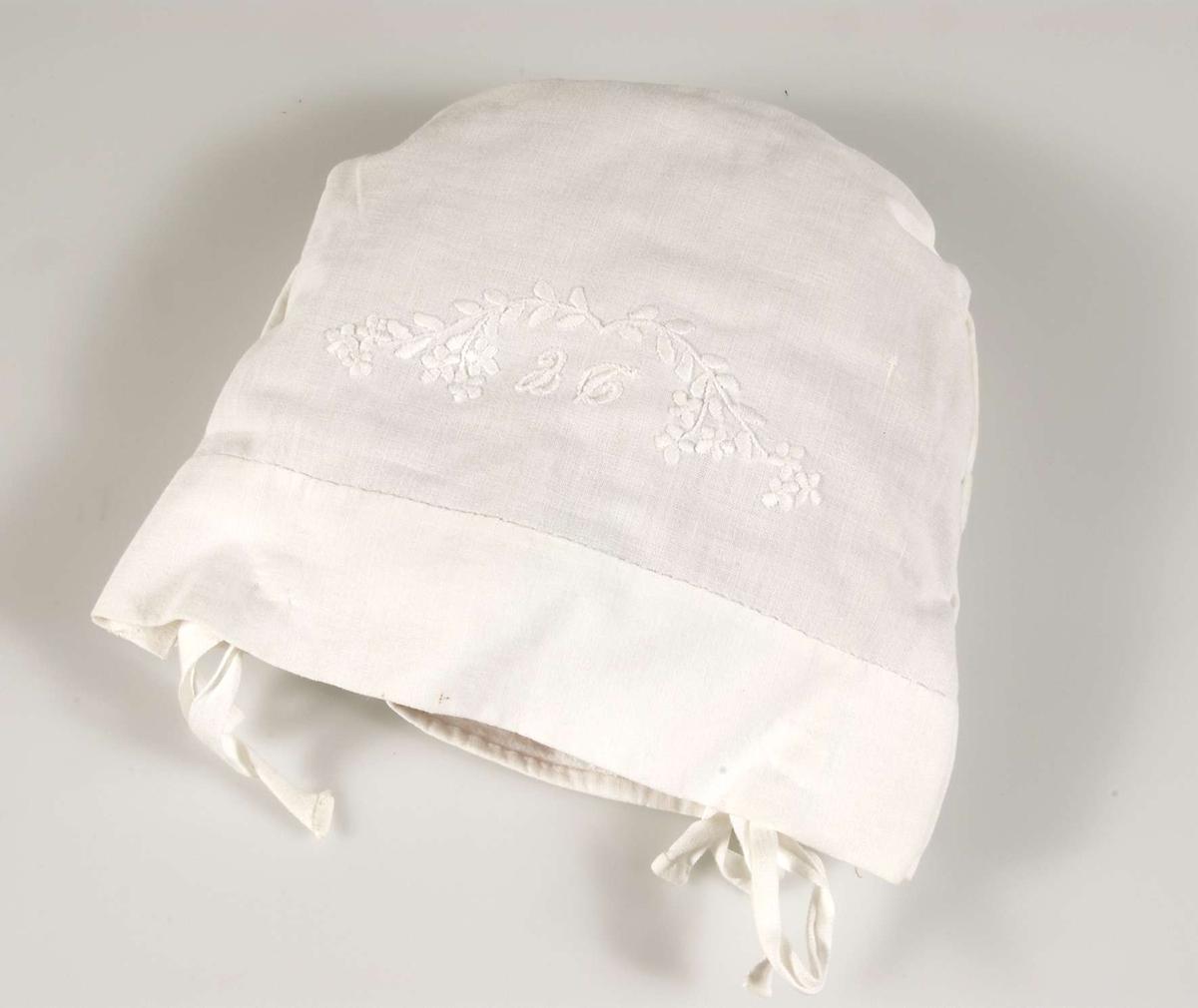 Kudde ingående i sängkläder till docksäng (vagga UM40571). Röd, rund, stoppad innerkudde med vitt, broderat örngott. Initialerna EC broderat på örngottet. Till sängkläderna hör också täcke, underlakan och madrass (UM40573a, c-d).