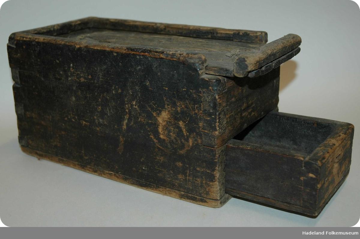 Kasse med skuff med 2 rom og uttrekkbart lokk. Løkke utskåret i en snipp.