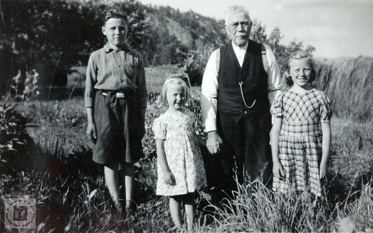 Bestefar med tre barnebarn på Håland. Grindheim.