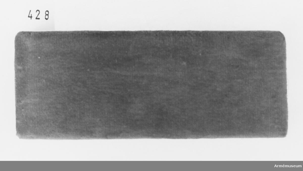Samhörande nr är 294-299, 321-350, 400-448 (427-428). Etui t nyckelkedja, Egypten. Sammetsklätt med förgyllt plåtspänne. Locket invändigt klätt med vitt siden. Överklädd krok att fästa berlocken i asken. Mottagen vid besök vid 2. egyptiska armén (Kanthara) i smb med inspektion av svenska UNEF-kontingenten nov 1974.