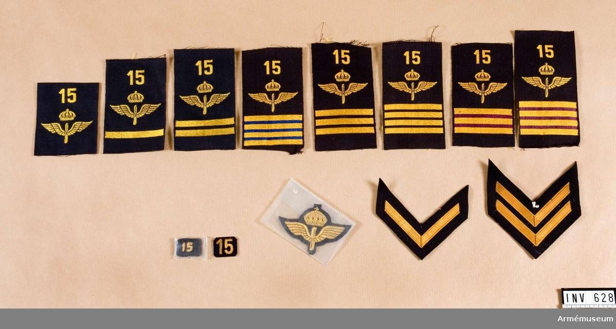 Låda med flygemblem, F 15. Diverse flygemblem: m/30 = ärmemblem m/30, m/51 = axelhylsor m/51 m/58 = axelhylsor m/58 Till ... finns: rustmästare, 100 st m/51; Överfurir, 300 st m/30, 200 st m/51 och 500 st m/58; Överfurir, tekniker, 300 st m/30 och 200 st m/58; Överfurir, flottiljpersonal, 100 st m/30; Furir, 100 st m/30 och 200 st m/58; Furir, teknisk personal, 200 st M/30 och 200 st m/51; Korpral, 100 st m/51; Vice korpral, 100 st m/51; Menig, 200 st m/30 och 400 st m/58. Gradbeteckningar för överfurir (fyra större tecken), furir (tre  streck), korpral (två större streck), vice korpral (två större  streck) och menig utan streck.