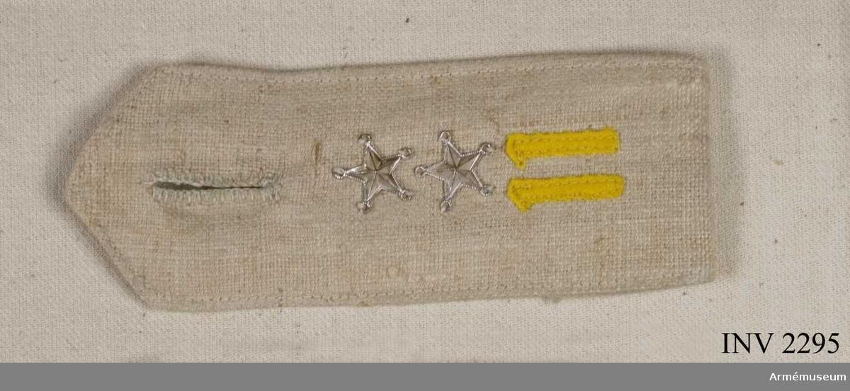 """Vitt linne, dubbelvikt. Knapphål vid inre sidan mot halsen, för  att knäppas fast vid pälsen. På översidan med """"11"""" i gult kläde  och två silverstjärnor = löjtnants grad. """"11"""" är regementets nr, I 11."""