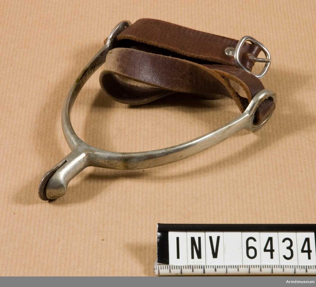 Av förnicklat stål. Med hals och slättrissad hjulsporre. Rem av brunt läder (och bärs följaktligen till bruna skodon; i detta fall AM.006418 - AM.006419).