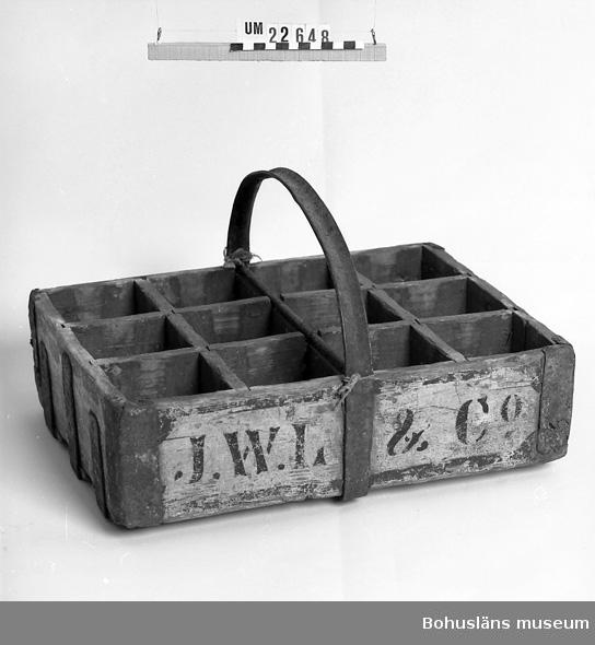 """594 Landskap BOHUSLÄN  Träback med ribbor som bildar tolv avbalkningar för flaskor. På yttersidan hörnen järnförstärkta och gavlarna med järnband. Grönmålad.  På ena långsidan texten: """"J V L & C O."""" Böjt järnband som handtag, fastsatta på backens undersida.  UM 128:6"""