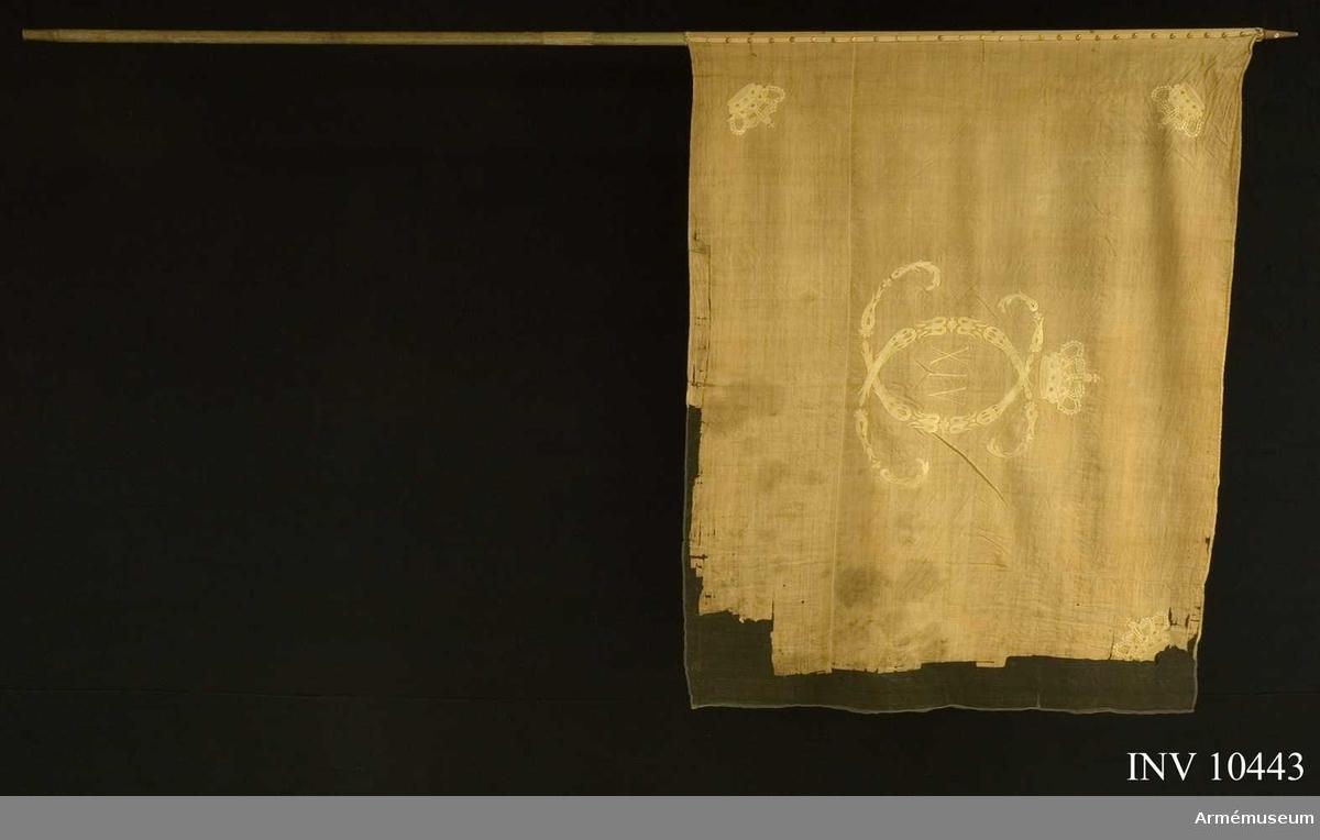 Grupp B.  Fanduk av vit linnelärft varå broderat omvänt lika å båda sidor Karl XIV:s namnchiffer, av små ornament bildat dubbelt C varinom  XIV under sluten krona med rött foder i hörnen liknande kronor kantad med vitt linneband, fäst med liknande band och förgyllda spikar. Kronorna har ursprungligen haft rött foder. Stång av gråvitmålad furu. Holk saknas, den tillspetsade stången är 7,5 cm. Doppsko 7 cm av mässing. Stångens diameter ovan fanan 2,8 cm, nedom fanan 3 cm.