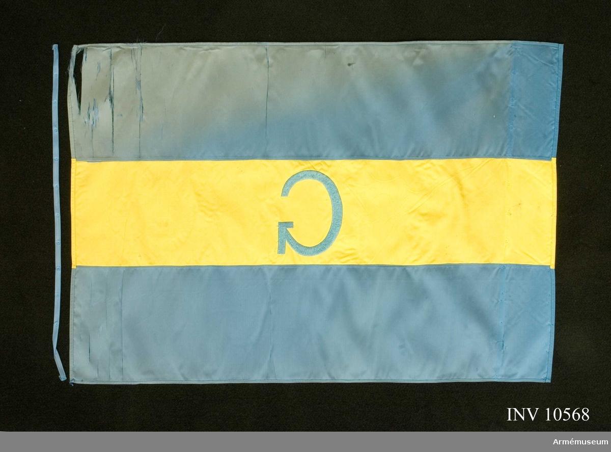 Grupp B I.  Enl. go 3596/1951. Sydd av fansiden med de två yttre fälten blå och det inre  fältet gult med ett broderat G i blått silke. Avtagen från sin stång. Spikbandet löst bredvid. Det blå sidenet skört och trasigt i yttre kanten. Det gula mitt- partiet helt (1971).