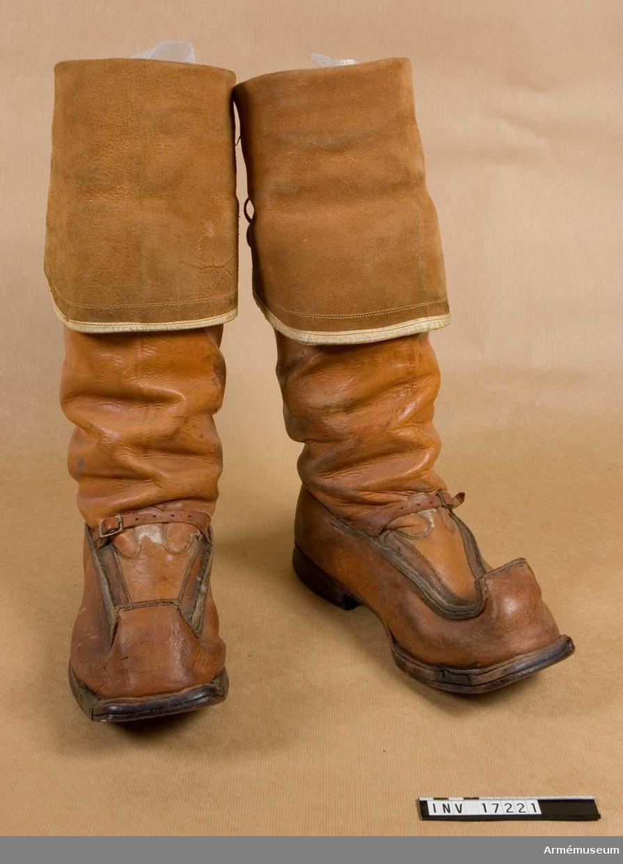 Grupp C I. STÖVLAR - finska (Lapplands) modell av ljusbrunt juftafålens skinn med upphöjda spetsar - (näbbstövlar). Skaften äro långa (över knäna). Stövlarna äro passande för skidåkning och för sumpmarker. Ovanpå vristen finns en rem med spännen för att stövlarna skola sitta fast på fötterna.