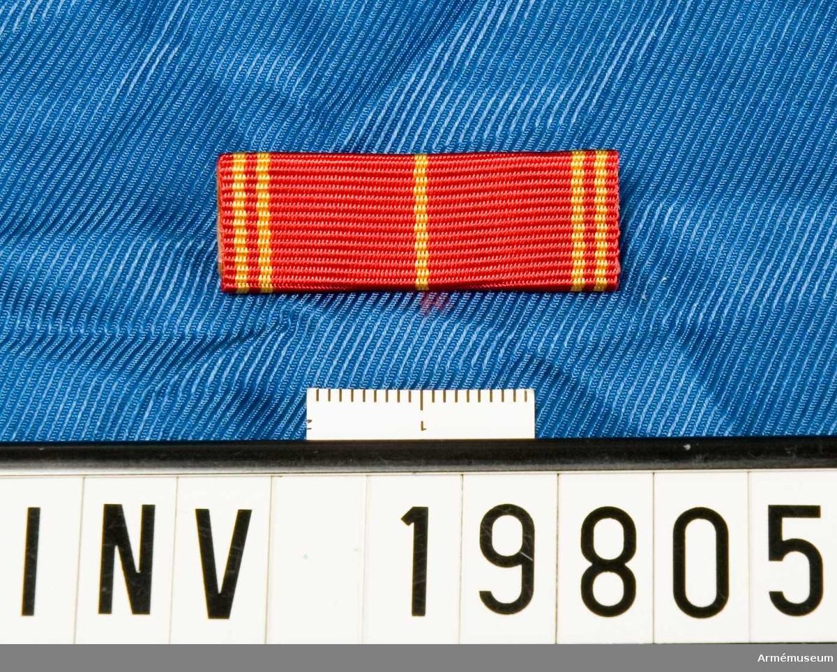 Rött band med ett gult streck i mitten och två gula streck på vardera sidan. Släpspännet förvaras i ask tillsammans med en medalj och en miniatyrmedalj.