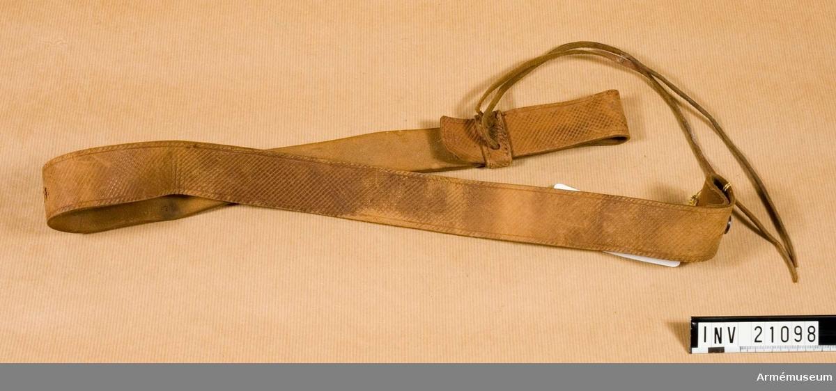 Grupp C II Av brunt läder. Löpare med läderband, på ena änden järnknapp och knapphål.