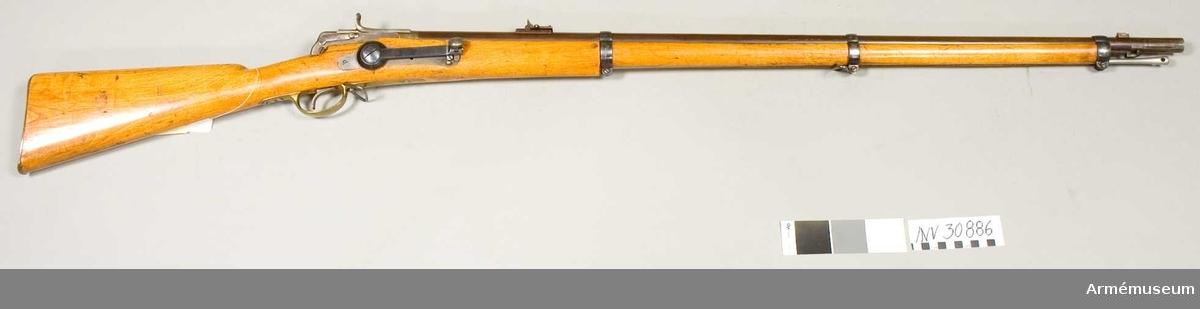 """Grupp E II. Antal refflor 6 st. Räffelstigning 1 varv på 112,8 cm.  """"Hagströms andra modells andra typ"""", prövad 1865.  Pipan är brungjord och av samma typ som på kammarladdningsgevären m/1864, men saknar bajonettklack. Anordningen för bajonettfastsättningen är av preussisk typ. På pipans undersida 10,7 cm bakom mynningen sitter ett kraftigt häfte för bajonettfjädern, som är 9,5 cm lång och fasthålles av ett stift. Längst fram är fjädern utvidgad till ett efter pipans rundning avpassat handtag, vilket står ut litet från pipan. Bakom handtaget har fjädern på insidan ett skarpt, tvärgående spår. Kornet och kornklacken äro av m/1864. Vinkelklaffsiktet sitter 12,5 cm framför pipans bakände. Den längre klaffen är utbildad till ett med löpare försett ramsikte, som dock ej är graderat. Längst bak på pipans översida står ett krönt C, på vänstra sidan 77 samt på undersidan WN, 2, P och WN.  Mekanismen är en förbättring av den på AM 4540. Slutstycket är 10,5 cm långt och har på översidan en längsgående ränna. Längst bak på undersidan har detsamma ett par parallella klackar, vilka genombrytas av ett hål och som stå på ett avstånd av 1,3 cm från varandra. Dessa klackar placeras på var sin sida av den från svansjärnet utgående klacken. Genom hålen i slutstyckets klackar och genom hålet i svansjärnets klack går en skruv, kring vilken slutstycket är rörligt. Litet bakom framänden går från slutstyckets undersida en kraftig klack nedåt och litet bakåt. En annan, tunnare klack går parallellt med den förstnämda omkring 1,3 cm längre bak. På högra sidan är ytan på den främre klacken både nedtill och baktill nedfilad omkring 5 mm. Även på den bakre klacken är högra ytan nedfilad omkring 5 mm men längst ned finnes en cirka 5 mm hög tand kvarlämnad. Nedfilningen fortsätter cirka 6 mm bakom bakre klacken samt går dessutom en bit upp på slutstyckets högra sida. Längst fram har slutstycket ett 5 mm långt munstycke, vars diameter är 15 mm. Munstycket har tätringen av stål. Nedtill på slutstyck"""