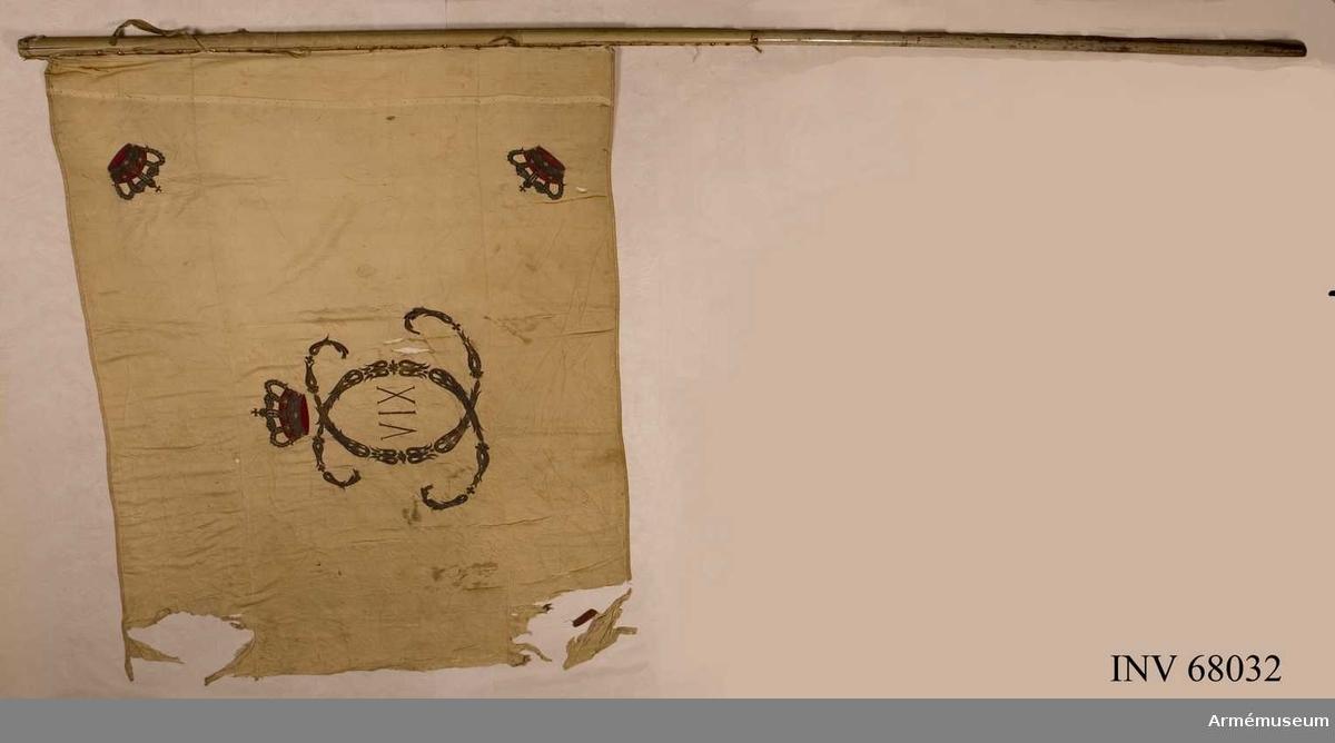 Duk: Tillverkad av cremefärgad sidenkypert, sydd av tre horisontella våder. Fäst vid stången med en rad tennlickor på ett vitt band.  Dekor: Broderat omvänt lika på båda sidor i guld Karl XIV Johans namnchiffer, små ornament bildande dubbelt C och i mitten XIV, krönt av en sluten krona med rött foder, liknande kronor i hörnen. Kantad med vitt sidenband.   Stång: Tillverkad av vitmålad furu.