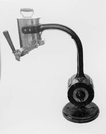Lacksmältningsapparat, elektrisk, av tysk tillverkning. Apparaten står på ett cirkulärt podium av mörk metall. Ett stag reser sig rakt upp från podiet, och nedtill finns elmotorn innesluten i en cylindrisk metallbehållare. På ena sidan finns möjlighet att sätta av och på apparaten. Staget fortsätter vidare uppåt från cylindern,innan det viker av, och i ändan bildar en klyka. I klykan sitter fastskruvad en behållare med lock, vari man lade ner lacket. Behållare i vitmetall. Från cylindern löper en sladd upp till denna behållare längs staget. Nederst på behållare en anordning för tappning av lacket, med ett handtag.