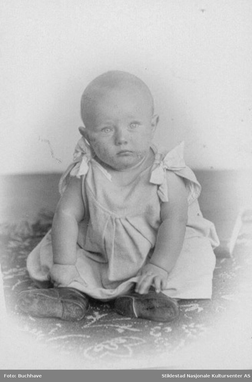 """Portrett av Halvdan F. Elstad sittende på golv i """"kjole"""" med knytting på skuldre, uten armer."""