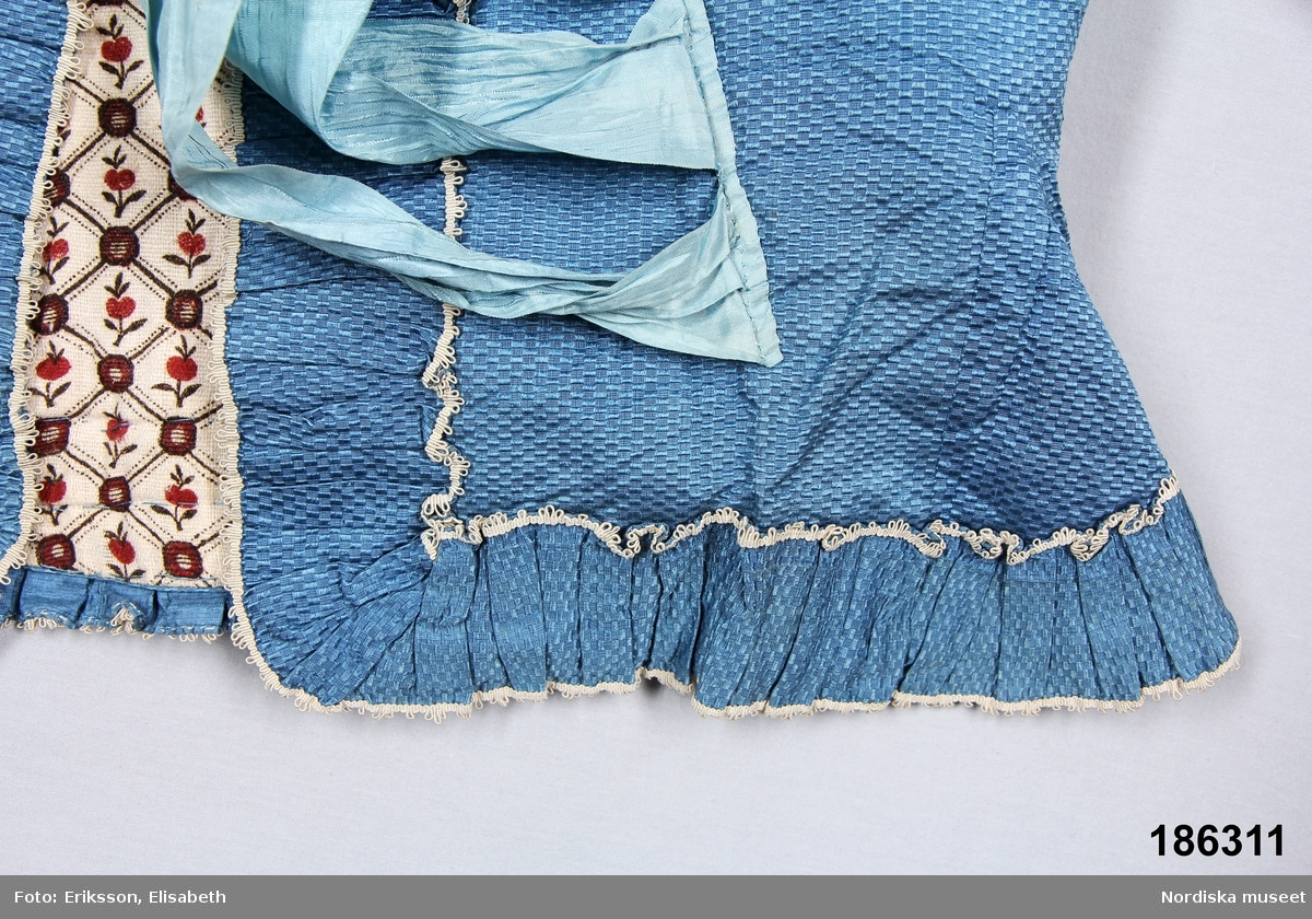 """Katalogkort: """" Kofta av blått siden fodrad och vadderad m. blommigt vitt tyg. Rund djup halsringning kantad med 5,5 cm bred rynkad slå m. vita snörmakeriband på ömse sidor. Nedre kanten och ärmen även kantade med slåar, på ärmen något bredare. Utsvängd nertill. Knyts med 4 par blåa sidenband, halvkorta ärmar.""""  Klarblått siden med skrovlig struktur, 2 framstycken, 2 bakstycken, infällda skörtkilar fram och 3 skörtveck i ryggen, isydd halvlång ärm med veckade breda """"uppslag"""". Veckade slåar av tyget kantade med smala vita gallerband runt hela koftan. Vadderad och fodrad med tryckt kattun av enklare fodertyp på oblekt botten med enkla stiliserade blommor i ett gallerverk i krapprött och brunsvart. Anm. I mycket gott skick /Berit Eldvik 2007-02-01"""