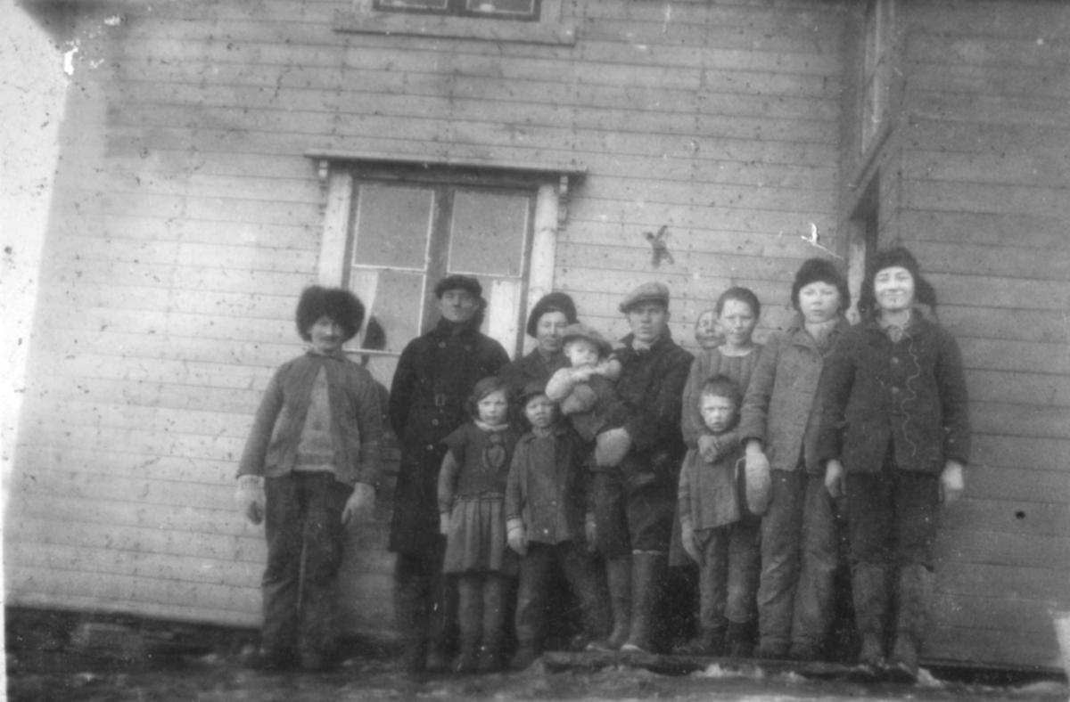 En gruppe mennesker poserer for fotografen utenfor et hus. Sted og personer er ukjent, men bildet kan være tatt i Kvalsund kommune.