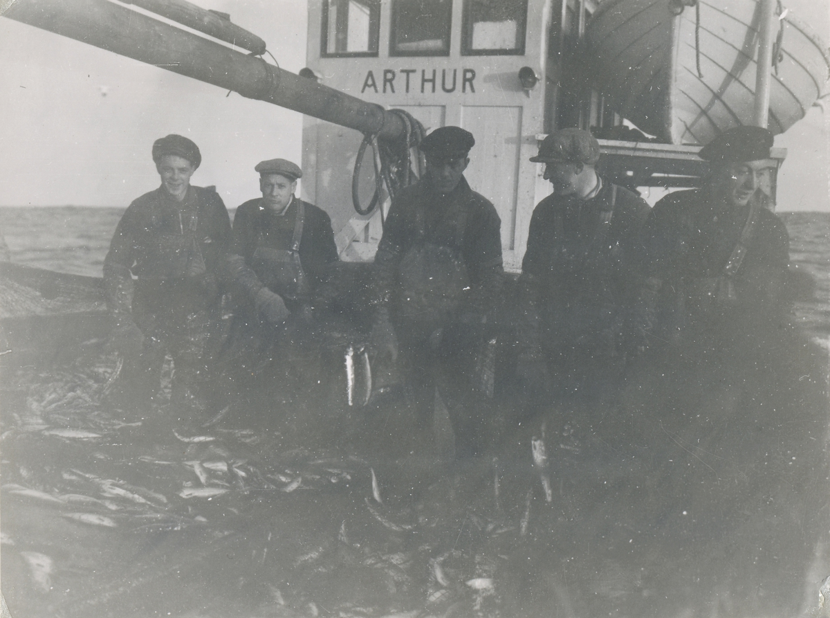 """En gruppe fiskere på Grønlandsfiske viser frem fangsten ombord fiskebåten """"Arthur"""". Motiv antagelig tatt ved Island."""
