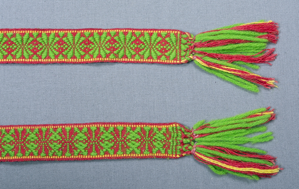 Klarlila bomullsförkläde med smala ränder i  svart, gult och grönt. Rynkat mot en linning av mörkblått tyg med grupperade vita ränder till en bredd av 29 cm.  Påsydda knytband i sidorna, röd botten med upphämtamönster i illgrönt ullgarn, avslutas med tofs av varpen. Längd i höger sida; 153 cm, längd i vänster sida; 140 cm. Handsydd och maskinsydd. Fållad nertill på maskin med tre raksömmar med gul tråd.