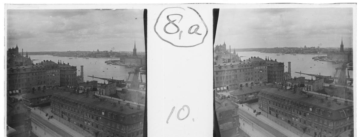 'Vy med byggnader och människor längs väg. I fonden båtar i vatten. :: Enligt text till fotot: ''View from Katarinahissen, Mälarsidan.'' (Utsikt från Katarinahissen mot Mälsarsidan.) ::  :: Ingår i serie med fotonr. 5237-5267.'