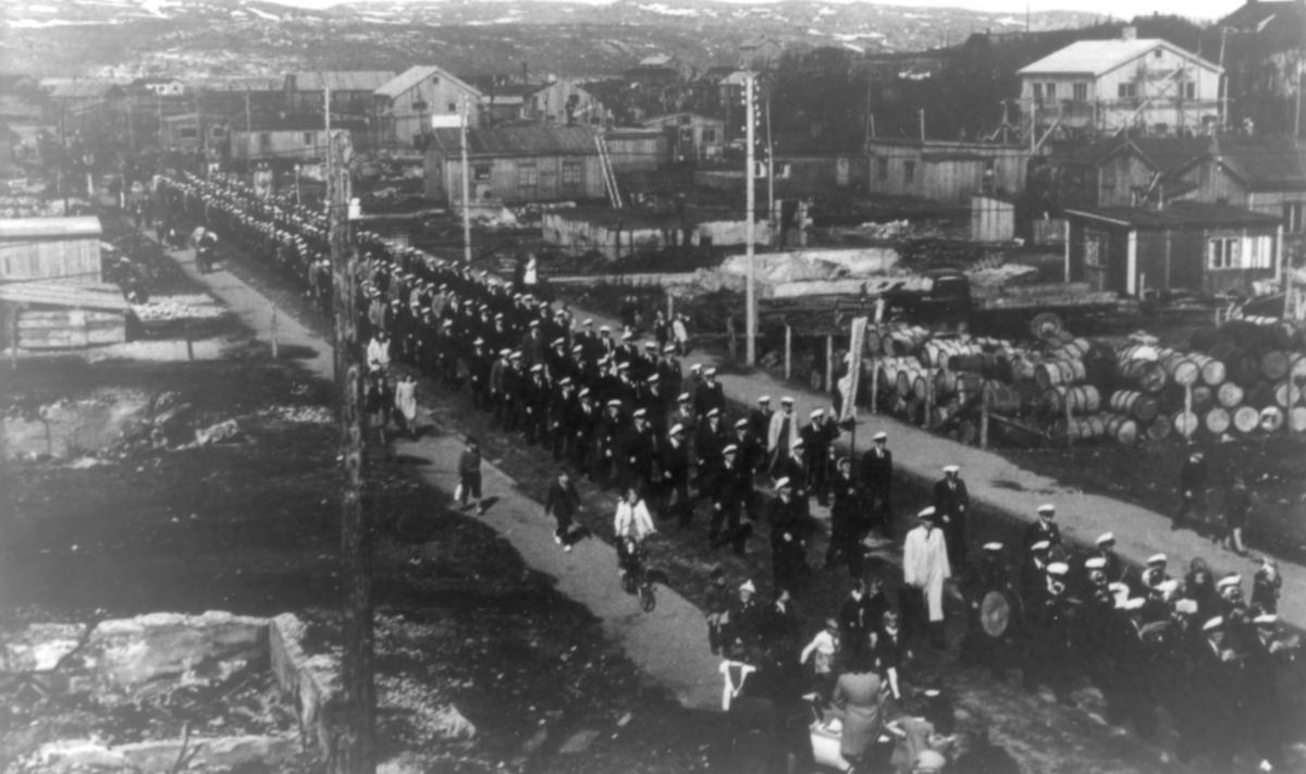 Sangerstevne i Kirkenes 1946. Bildet viser et opptog. På sidene av veien ser vi ruiner etter krigen. Husene er ennå bare brakker.