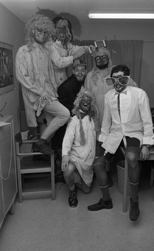 Luciafirandet 13 december 1966Sex unga män är utklädda i komiska maskeradkläder. En av dem bär en Luciakrona med ljus i på huvudet. En annan bär överdimensionerade glasögon. En står på en stol och en annan sitter på hörnet av ett bord. Resten står på golvet. Alla är målade i sina ansikten.