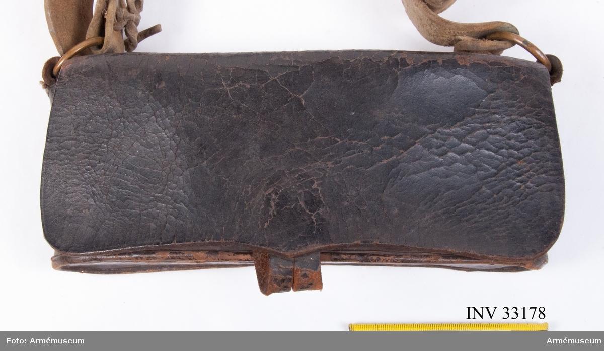 Grupp C II. Kartuschen innehåller en träkloss med borrade hål och rum för 14 patroner med kaliber mellan 8 och 12 mm. Det finns även en lös bleckplåt som har suttit som avdelare i väskan.