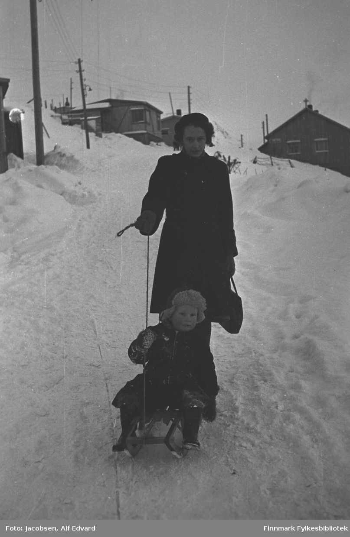 En vinterdag i Skolebakken i Hammerfest. Aase Jacobsen holder i tauet til kjelken der sønnen Arne sitter. Han har en mørk vinterdress, skinnlue med tykt ullfor og strikkevanter på seg. Aase har en mørk kåpe, mørk lue og mørke strikkevanter på seg. Hun har en mørk håndveske i venstre hånd og tauet til kjelken i høyre. Det er mye snø i terrenget. El-stolper står langs veien på venstre side av bildet. Helt til venstre på bildet ses hjørnet på et lite bygg. Litt lenger opp i bakken, oppe til venstre står et lyst hus med ganske flatt tak. Huset tilhørte Albert Hansen som var lastebileier. Et mørkt hus står øverst til høyre på bildet. Huset er forholdsvis mørkt med to vinduer i røstveggen. Deler av et gjerde ses delvis nedsnødd oppe til høyre på bildet. Mellom Alberts hus og bygget helt til venstre ligger Breilia skole idag.