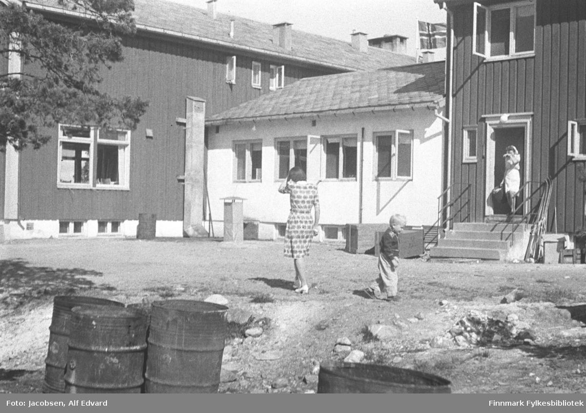 Bildet er tatt på en ferietur familien Jacobsen tok med buss i 1948 eller 1949. I følge Arne Jacobsen er dette bildet fra NNH's gjestgiveri i Alta. Aase jacobsen ståre med ryggen til kamera og har en mønstret kjole og hvite/lyse sko på seg. Sønnen Arne litt bak henne har en lys bukse og mørk genser på seg. To store bygninger med mørkt stående panel og hvite grunnmurer i solskinnet. Bygningen til høyre på bildet har flere vinduer med hvite karmer og vannbrett. En liten betongtrapp går opp til den åpne døra. Trappa har tynne metallrekkverk på begge sider og en trekasse står på bakken ved siden av den. Det grå nedløpsrøret til en takrenne ses på hjørnet av bygningen. I døråpninga står en dame i hvit/lys kjole. Hun bærer noe i høyrearmen. Til venstre på bildet står et stort bygg, ganske mørk stående panel på det og. Bygget har to store og tre små vinduer på langveggen som vises på bildet. To små vinduer på grunnmuren har også hvite karmer. Bygningen har skiferdekke på taket og der ses også flere luftepiper. Mellom de to store bygningene står et mindre, hvitt bygg som er bygd fast i dem. Fire vinduer står på langveggen, to av dem åpne. Plassen foran bygningene er stort sett flat med kort gress. En liten sti går nedover mot kamera og nærmest står fire oljefat. Greiner fra et stort tre ses øverst til venstre. Det norske flagg ses over taket på den midterste bygningen.