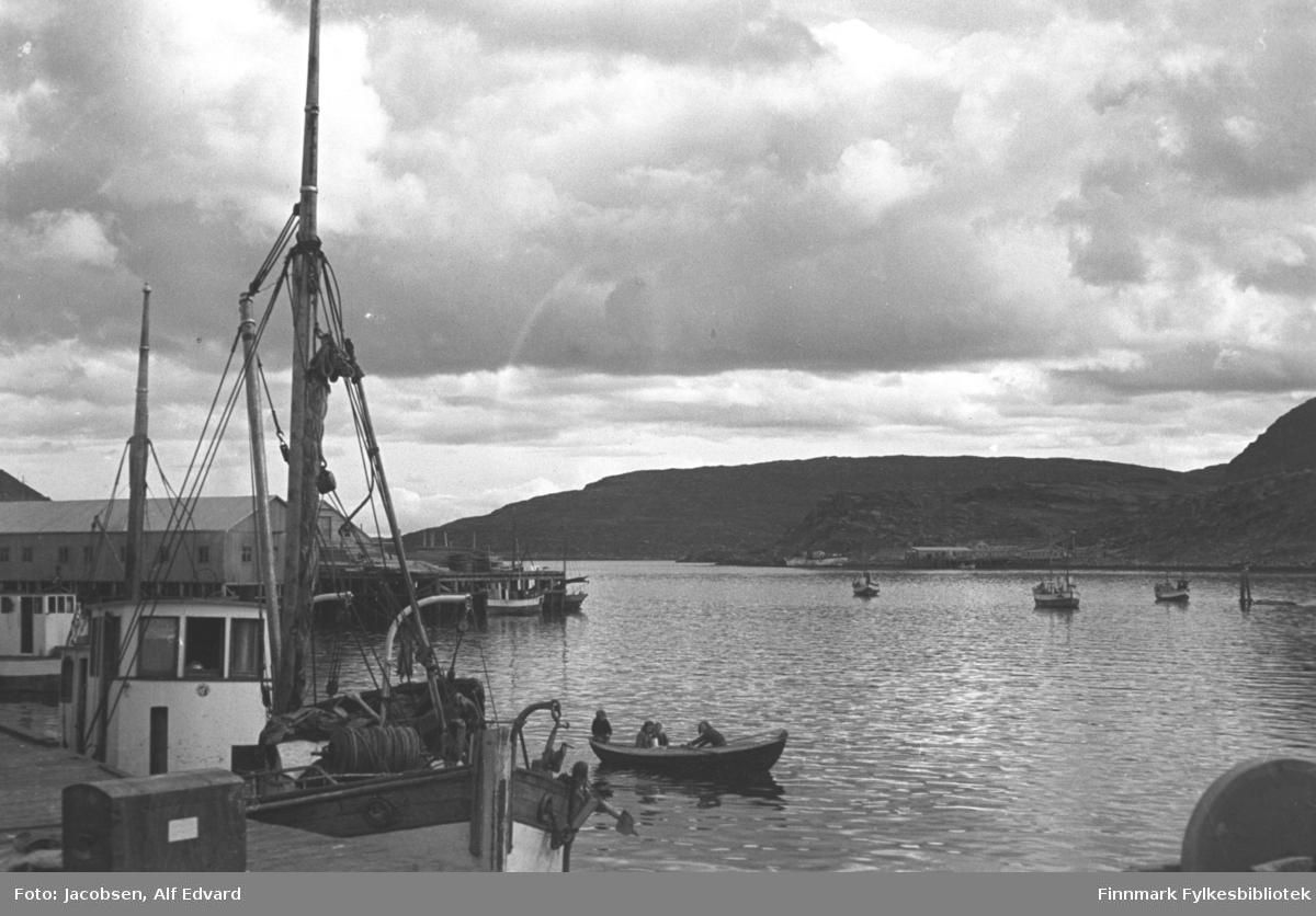 En vindstille, men overskyet sommerdag på havna i Havøysund. En båt ligger ved kaia nærmest. Båten har hvitmalt styrhus og en stor mast med bom foran og en mindre mesanmast bak. Foran på baugen står trommelen til vinsjen og litt av dreggen kan også ses. En kasse står på kaia ved siden av båten. På havna rett utenfor ligger en robåt med tre personer ombord. Robåten er av tre og har et hvitmalt bord ved rekka. En avlang brakke står på en kai til venstre på bildet. Det er Anton Olsens materialhandel som senere ble omgjort til fiskemottak. Det hvite styrhuset til en båt ses liggende ved den kaia. Et mindre fartøy ligger ved kortenden av kaia. Utpå havna ligger flere båter fortøyd og et sjømerke står langt ute på havna, helt til høyre på bildet. Et fjellparti ligger tvers over havna. Bygget som ses i strandkanten der er Haagensen-bruket.