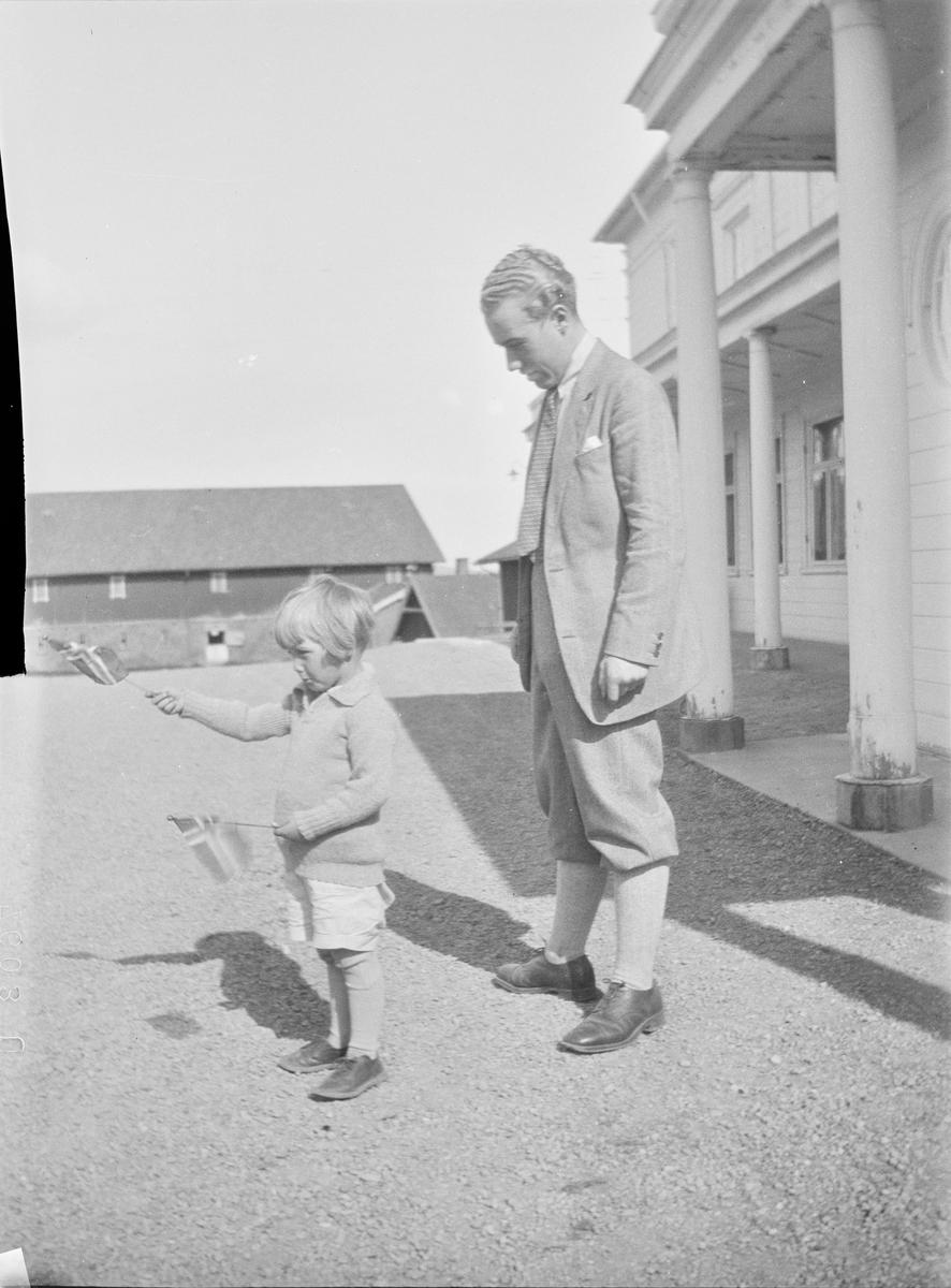 Iacob Ihlen Mathiesen står på gårdsplassen utenfor svalgangen til hovedhuset på Linderud Gård sammen med et barn som vifter med ett norsk flagg i hver hånd.