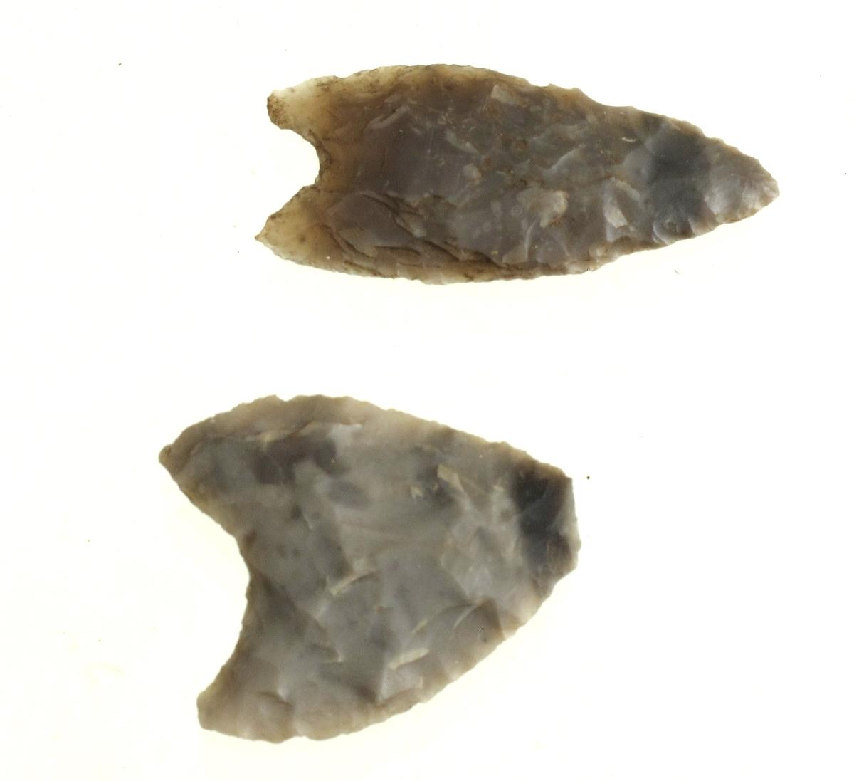 2 hjerteformete pilespisser av grå flint, den lengste nærmest som [Rygh fig.77]R. 77, men uten rygging, med st. bredde midt på bladet og med mindre avstand mellom flikene; den korteste nærmest som H. Gjessing: Rogalands Stenalder, fig. 191, men kortere og bredere.   Lengde h.h.v. 3,3 og 2,5 cm, bredde 1,5 og 2,2 cm.
