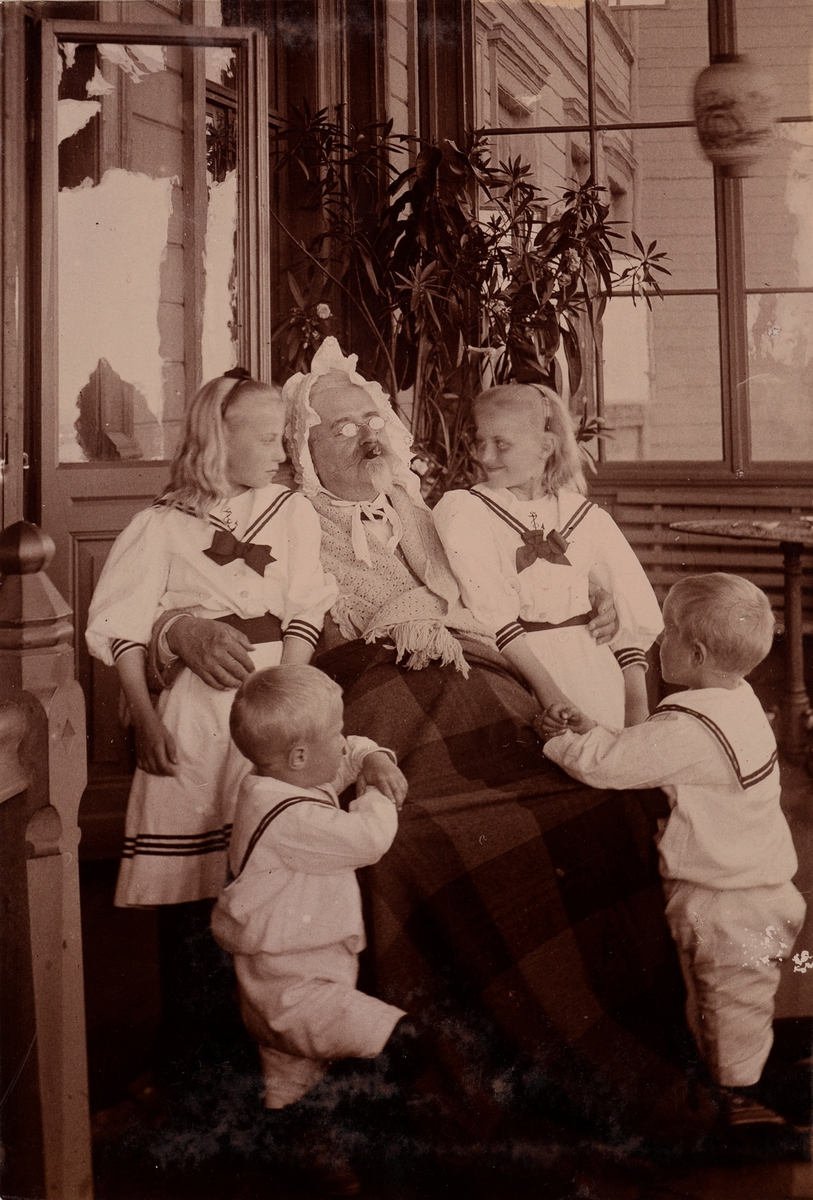 """Haagen """"Vesle"""" Mathiesen utkledd som """"gammel kjerring"""" leker med Christensen barna, mens han røyker sigar."""