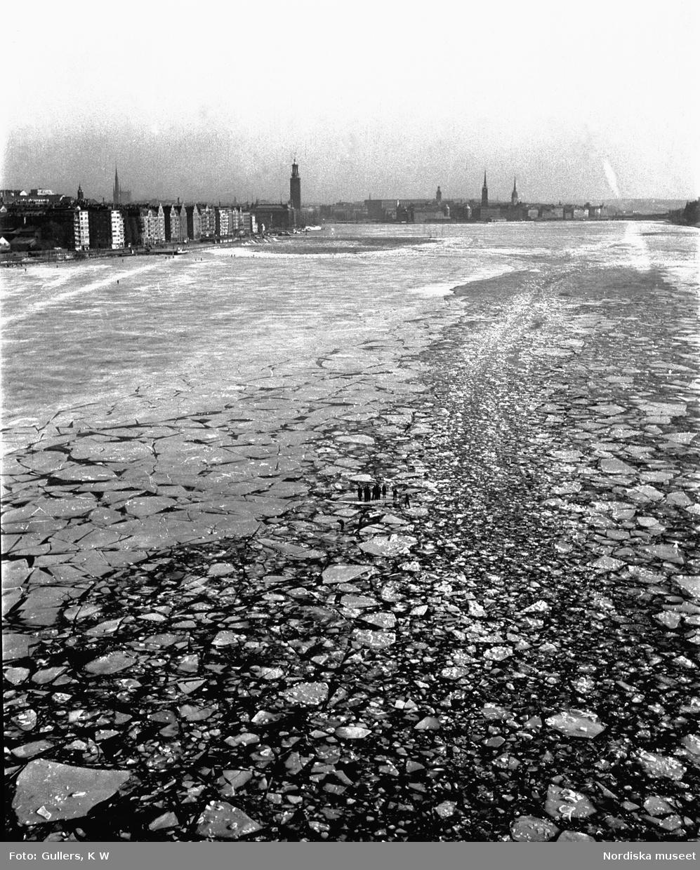 Vy från Västerbron över Riddarfjärden. Pojkar hoppar mellan isflaken i fartygsrännan.