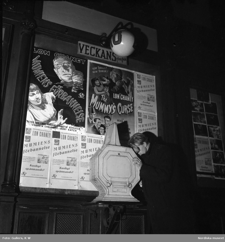 """Eng ung man pressar ansiktet mot ett tittskåp utanför biograf vid Birger Jarlspassagen, Stockholm. Filmaffischer för """"Mumiens förbannelse"""" (1944) på väggen."""