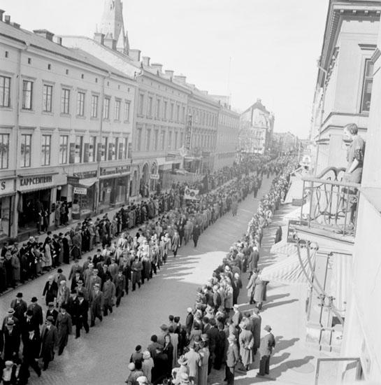 Förstamajdemonstration i Örebro den 1 maj 1937. Demonstrationståget går i riktning söderut på Drottninggatan. Det mycket långa förstamajtåget består av människor av olika slag. Några bär på röda fanor, plakat och banderoller. Åskådare kantar Drottninggatans båda trottoarer för att titta på demonstrationståget. Nikolaikyrkans torn kan skymtas ovanför hustaken till vänster i bilden. Närmast till höger står en kvinna på en balkong och tittar på evenemanget.