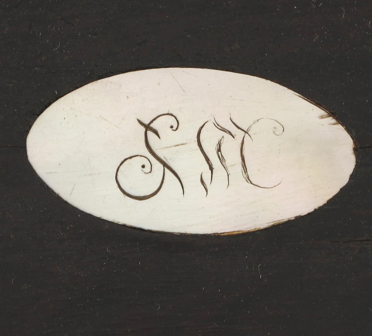 Perlemors oval midt på lokket/ Perlemors nøkkelskilt.