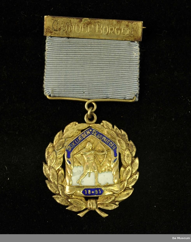 Medalje med lyseblått bånd, navneplate og laurbærkrans rundt et merke med skigåer med pil og spent bue.