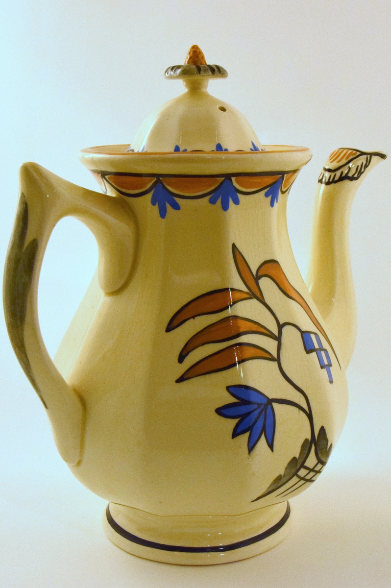 Servise i off-white glasur. Dekor RAKLER: kantet  i gultt/blått/sort mønster. Midtstilt dekor i tilsvarende farger og grått.