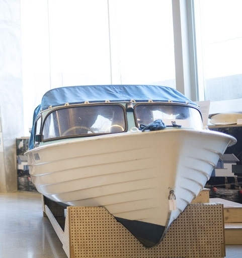 Hvit plastbåt med blå kalesje og turkist dekk. Innventar i tre, plast og isopor.