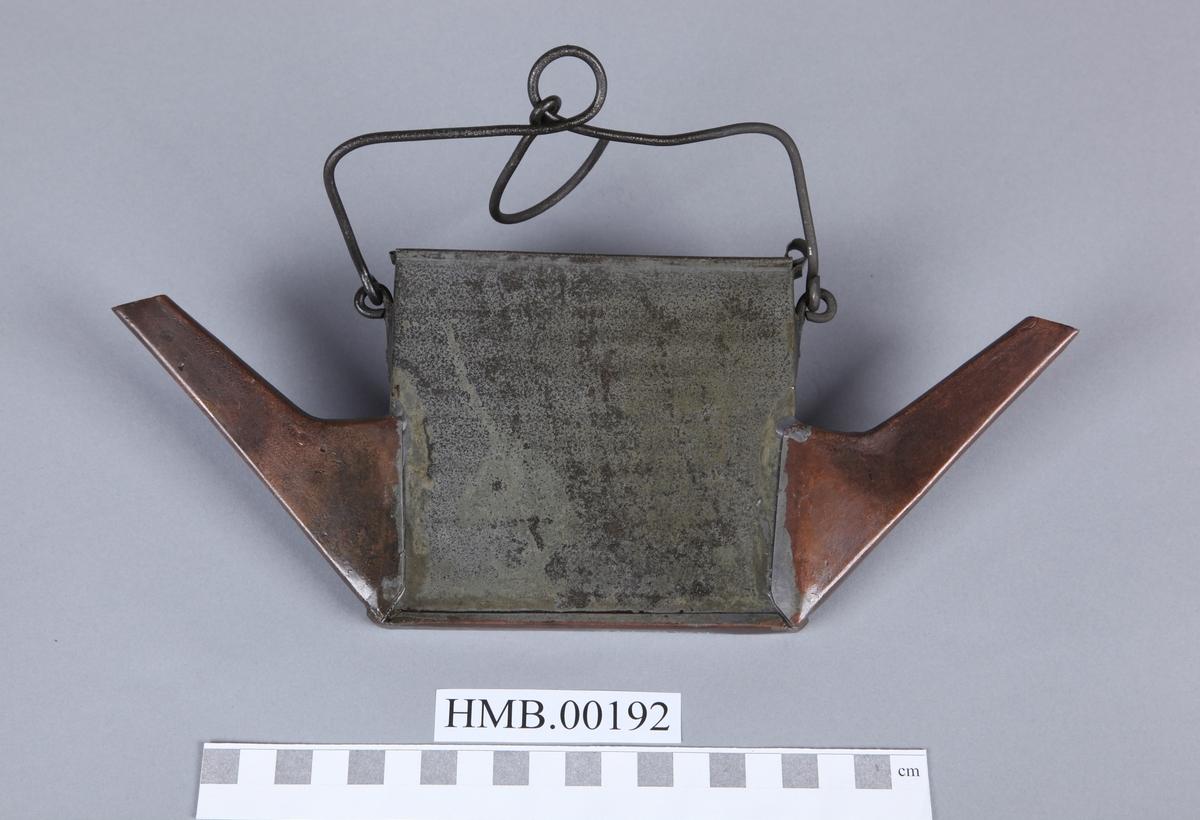 Flat, firkantet, to tuter. Nesten identisk med HMB.00181. Gjenstanden har skyvelokk. Tutene er laget av kobber, og det samme er bunnen. Tutene har en litt annen form enn HMB.00181. Hank har opphengsbøyle.