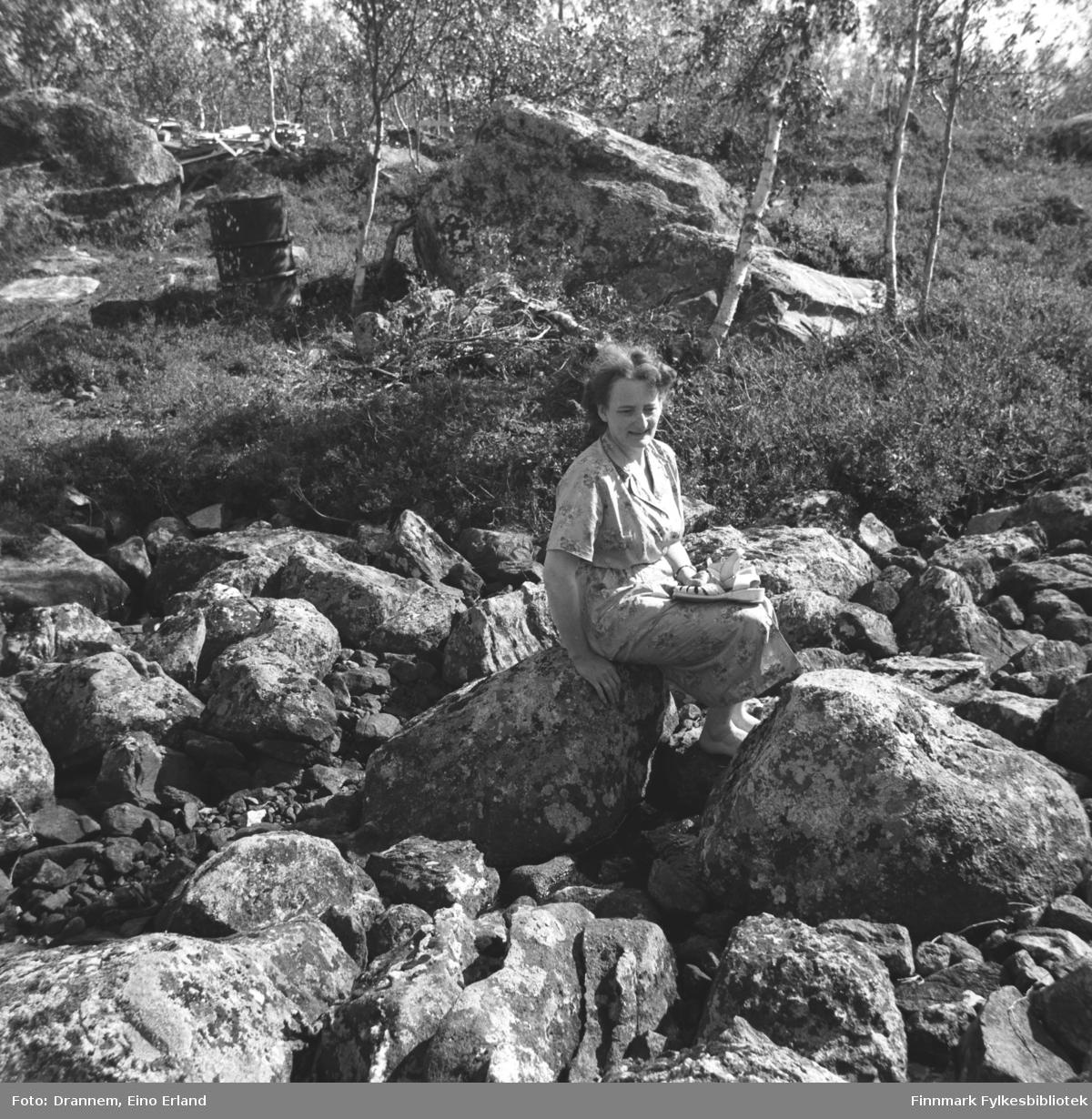 Olaug Gabrielsen sitter på en stor stein iført en kortermet sommerkjole.