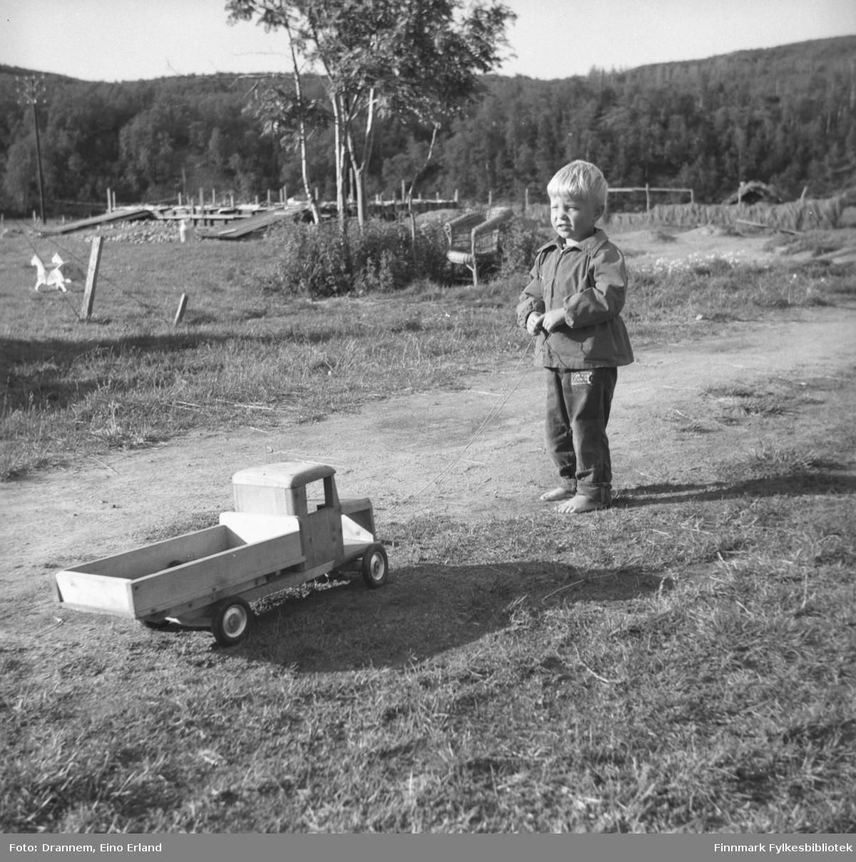 En lyslugget og barbeint Jarle Karikoski fotografert på et gårdstun  en sommerdag.