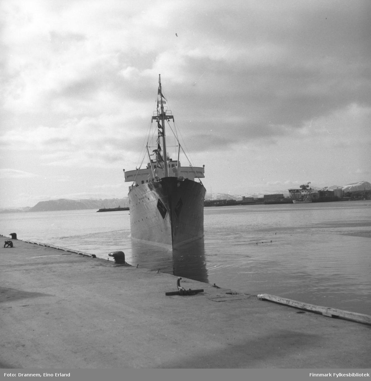 Et skip på vei inn mot Dampskipskaia i Hammerfest. Skipet ligner på MS Vesteraalens rederilogo på hver side av baugen.  Dette må derfor være M/S Vesterålen. På dette bildet ser man Fuglenesodden i bakgrunnen.