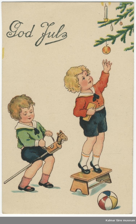 Vit botten. Två gossar, en rider käpphäst och en står på pall och sträcker sig efter ett äpple i en gran.