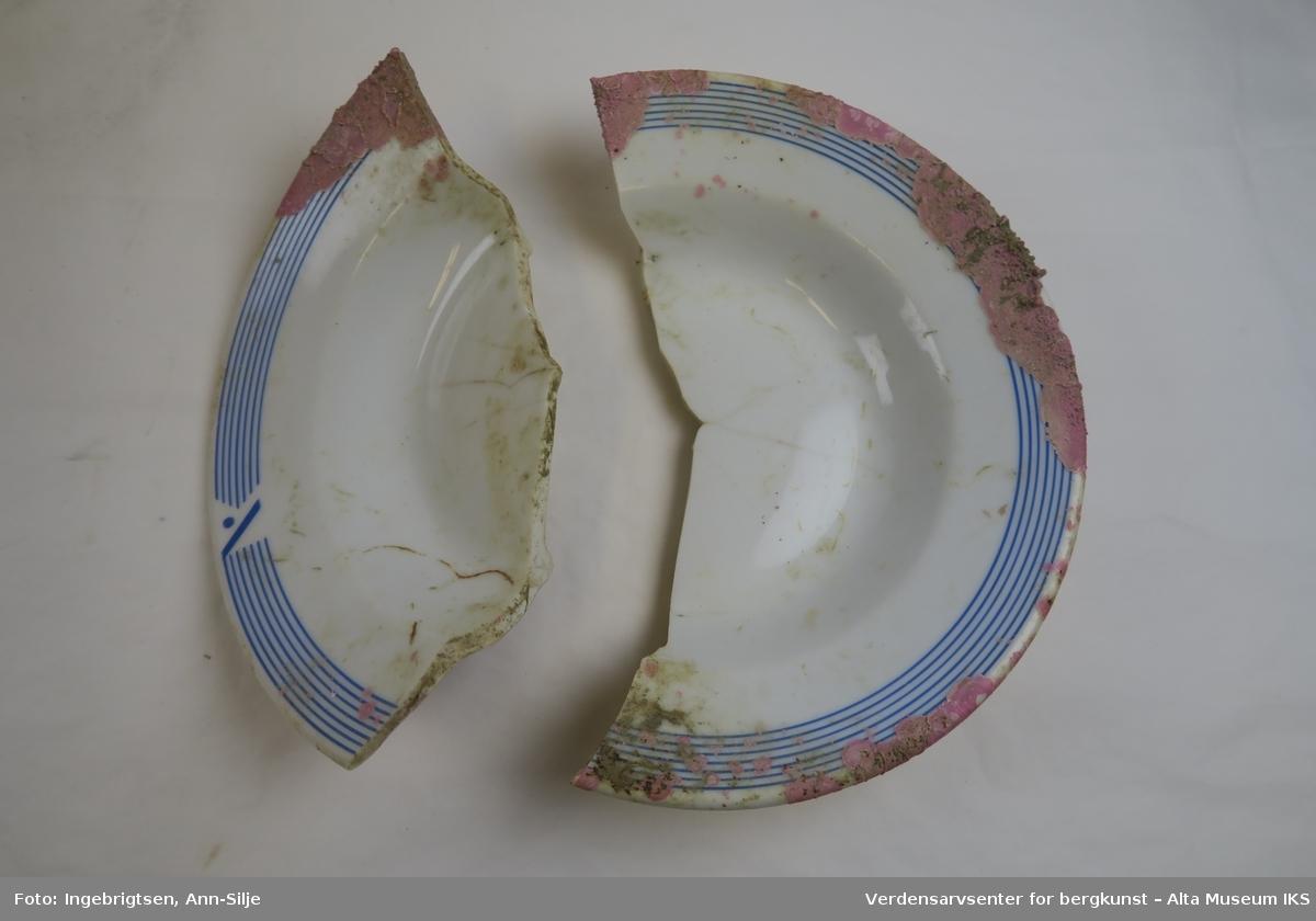 En dyptallerken som er knust i 2 deler. Rundt kanten er det 6 dekorlinjer i blått.